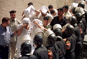 "Egyptian youths, charged with ""practicing debauchery with men"", cover their faces as they walk into court in Cairo 19 Septmeber 2001. The defendants, mostly in their 20's were arrested 11 May, on a Nile riverboat nightclub. The court, whose verdict cannot be appealed, could sentence them to as much as five years in prison if convicted.   (Film)   AFP PHOTO/Amr MAHMOUD   / AFP PHOTO / AMR MAHMOUD"